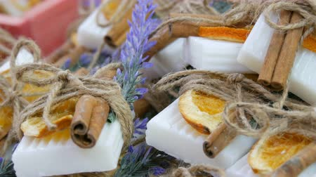 toeletta : Beautifully decorated white handmade soap with dried orange slices, cinnamon sticks and sprigs of lavender on store counter.