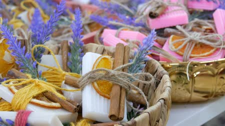 toeletta : Beautifully decorated white and pink handmade soap with dried orange slices, cinnamon sticks and sprigs of lavender on store counter.