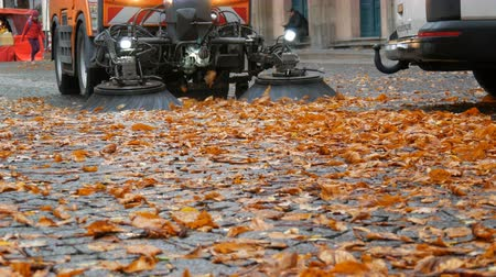 süpürge : Cleaning Machine brush removing yellow fallen leaves from the autumn street. Cleaning leaves in fall. Asphalt machine cleaning in Germany, Munich