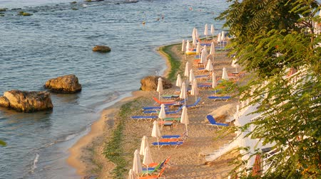 hajtogatott : Luxury vacation at sea. Empty multi-colored sun loungers or sunbeds and folded beach umbrellas on resort beach