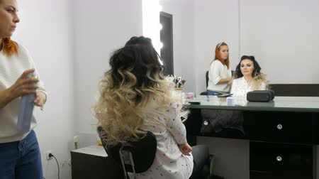 ondulação : Professional hairdresser stylist makes hair styling with a hairspray for a beautiful young woman with long hair dyed with ombre technique in beauty studio