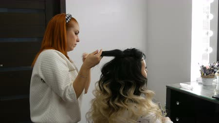 ondulação : Professional hairdresser stylist makes hair styling with a special comb to a beautiful young woman with long hair dyed using the ombre technique in beauty studio