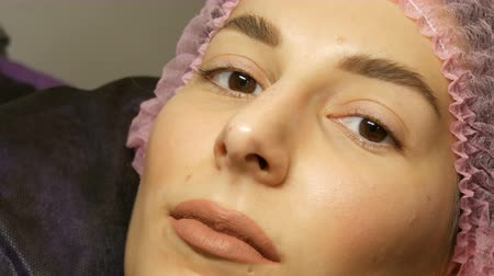 folt : The face of beautiful young woman with wide hairy eyebrows and brown eyes and matte beige lipstick on her lips in a pink hat before the procedure for laminating eyelashes in a beauty salon