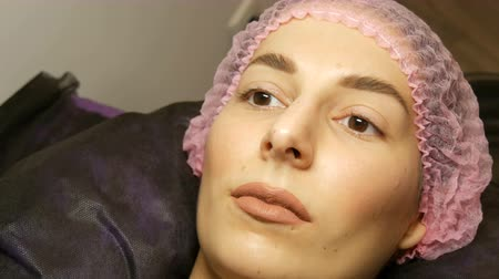 rozšíření : The face of beautiful young woman with wide hairy eyebrows and brown eyes and matte beige lipstick on her lips in a pink hat before the procedure for laminating eyelashes in a beauty salon