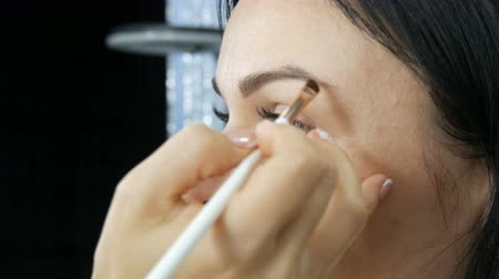 крупный план : Professional eye makeup. Stylist makeup artist applies makeup to young woman with a special brush in a beauty salon