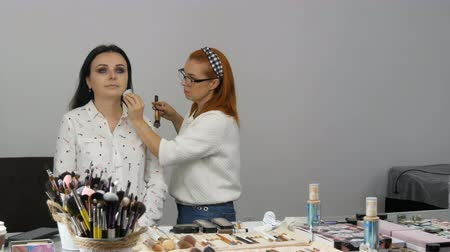 rímel : Red haired stylist makeup artist applies a special face cream with special sponge on the face of a young beautiful woman with blue eyes