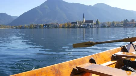 bavorské : A ferryman on wooden boat with an oar takes people to the other side, against the background of a beautiful picturesque church on Lake Tegernsee, Bavaria Dostupné videozáznamy