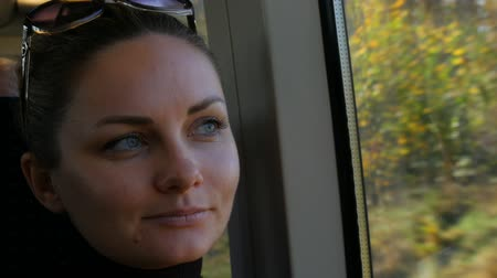 tramwaj : Close up portrait of beautiful young woman with green eyes and long black eyelashes rides in train looking dreamily and thoughtfully out the window. Outside window is colorful autumn foliage.