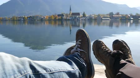 remo : Travelers couple hiking boots on mountain near Lake Tegernsee on the church background. Man and woman family trekking shoes. Pair sitting and making feet selfie on beautiful landscape. POV traveling
