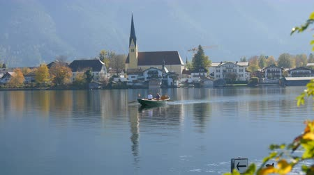 bajor : A boat ferryman ferries people to the other side, in the background of beautiful, picturesque church on Lake Tegernsee, Bavaria, Germany Stock mozgókép