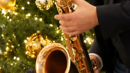 симфония : Nuremberg, Germany - December 1, 2018: A saxophonist playing a golden saxophone in mall or shopping center on the background of Christmas trees