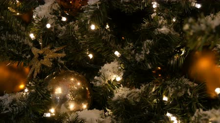 festoon : Beautifully decorated Christmas tree with large gold and silver balls, stars, garlands and artificial snow is standing in the shopping center close up view Stock Footage