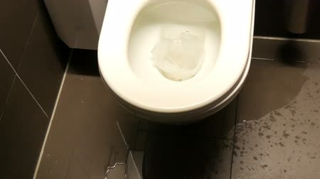 emperrado : A clogged ceramic white bowl toilet with paper, Water spreading on the floor