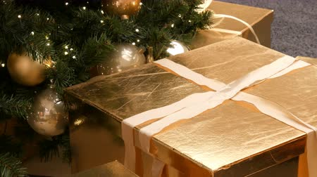 축하 해요 : Large gift boxes, present of gold color under the Christmas tree in the mall. Christmas and New Years gift decor. Gift gold box with gold satin ribbon.