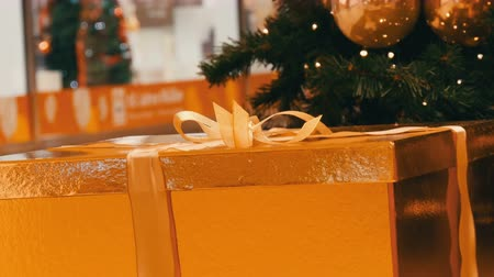 felajánlás : Large gift boxes, present of gold color under the Christmas tree in the mall. Christmas and New Years gift decor. Gift gold box with gold satin ribbon.