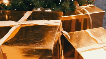 offrande : Large gift boxes, present of gold color under the Christmas tree in the mall. Christmas and New Years gift decor. Gift gold box with gold satin ribbon.