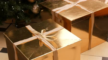 blahopřání : Large gift boxes, present of gold color under the Christmas tree in the mall. Christmas and New Years gift decor. Gift gold box with gold satin ribbon.