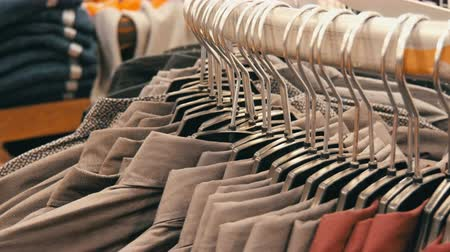 устроенный : Row of various fashionable mens shirts on a huge hanger in the mens clothing store in the shopping center.