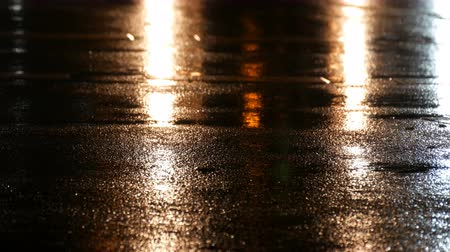 hurry up : Cars in traffic, headlights in rain on asphalt, view below. Rain hits the puddles at night. Reflection of cars lights Stock Footage