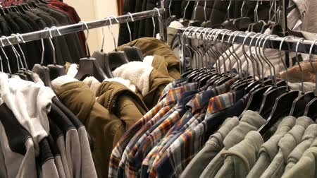 販売の : Nuremberg, Germany - December 3, 2018: Mens fashionable and stylish clothes on hangers in a clothing store in a mall
