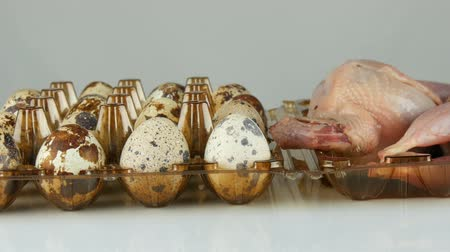 fürj : Fresh meat of quail in a plastic brown tray next to the quail eggs on white background