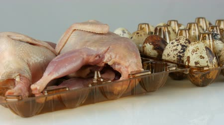 açougue : Fresh meat of quail in a plastic brown tray next to the quail eggs on white background rotate