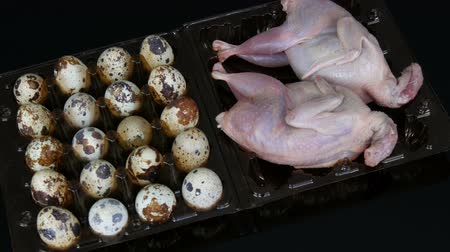 bird eggs : Fresh meat of quail in a plastic brown tray next to the quail eggs on black background