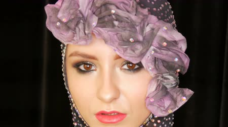 pink flowers : Portrait of a stylish high fashion girl model with expressive makeup smoky eyes posing in the studio on a velvet black background and reflector in eyes