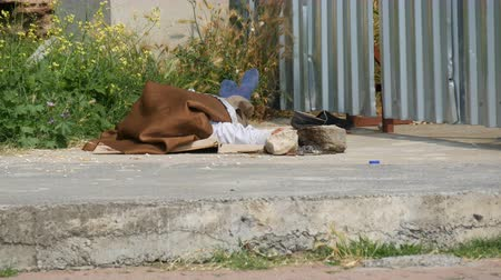 бездомный : Homeless man lies and sleeps on the street under fence covered with material from sun
