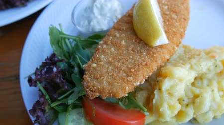 打者 : Two portions of beautifully cooked fish in batter on white plate in an expensive restaurant. Near the national Bavarian potato salad and greens with lemon