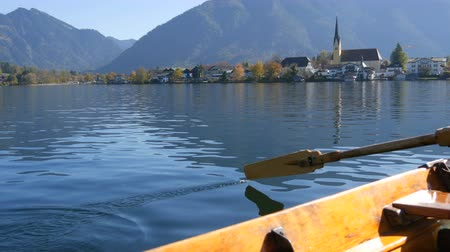 kano : A peaceful picture a wooden boat with an oar floats on beautiful mountain lake Tegernsee against backdrop of Alpine mountains and the picturesque container of the church. Ferryman ferries people