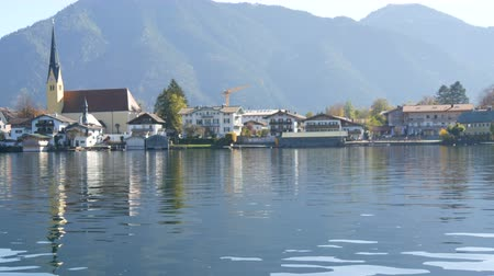 утки : Beautiful view of the Tegernsee lake in Bavarian Alps. Old church by the lake and mountains Стоковые видеозаписи