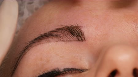 corrections : Microblading eyebrow tattoo, permanent makeup. Master in gloves, using special needle, injects pigment into the skin and stains the eyebrows using hair technique, making them natural, close-up view