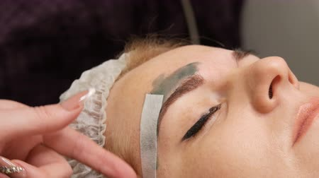 microblading : Wax correction of the shape of the eyebrows. Beautician applies warm green wax on eyebrows and removes excess hair with special strip.