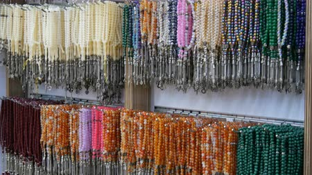 для продажи : Multi-colored beads from various natural stones hang in jewelry store in Istanbul. Colorful beads necklaces fashionable womens statement jewelry Стоковые видеозаписи