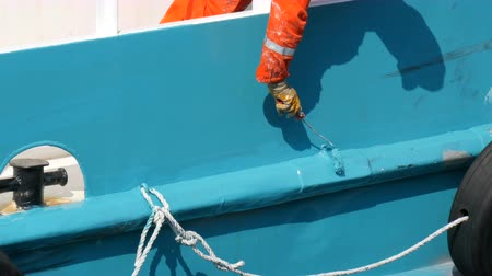 resistant : Hand of a man of a sailor paints with a paint with a roller stern of ship or boat with blue paint