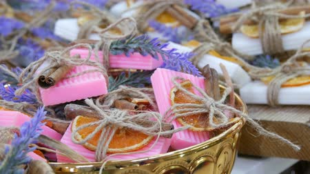 туалетные принадлежности : Beautifully decorated white and pink handmade soap with dried orange slices, cinnamon sticks and sprigs of lavender on store counter.