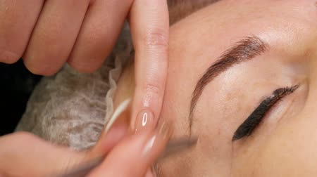 tatuagem : Special tweezers pluck eyebrow hairs. Eyebrow correction in beauty salon Stock Footage