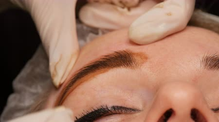 маркировка : Microblading hair brow. Eyebrow tattoo and permanent makeup. Master in the gloves evenly applies pigment to eyebrow skin