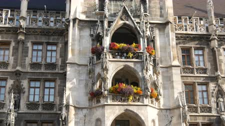 münchen : Munich, Germany - October 25, 2019: new town hall in Munich is decorated with a variety of blooming flowers. Marienplatz, the central square of the city Stock mozgókép