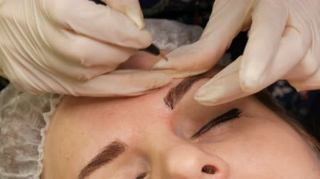маркировка : A beautician in gloves, using a special needle, applies a coloring pigment under skin of the eyebrows. Eyebrow shape correction using hair microbleeding, permanent make-up, eyebrow tattoo