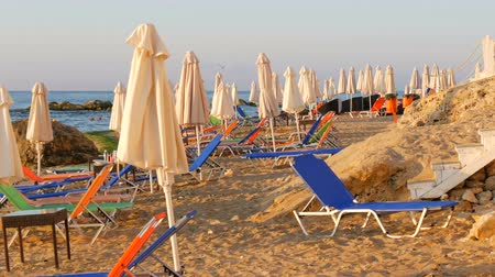 empty beach : Luxury vacation at Black Sea, Bulgaria. Empty multi-colored sun loungers or sunbeds and folded beach umbrellas on resort beach Stock Footage