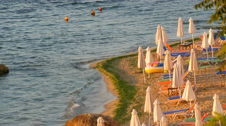 hajtogatott : Luxury vacation at Black Sea, Bulgaria. Empty multi-colored sun loungers or sunbeds and folded beach umbrellas on resort beach Stock mozgókép