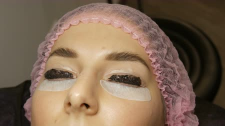 dyeing : Young woman lies on the procedure for dyeing eyelashes with special black paint