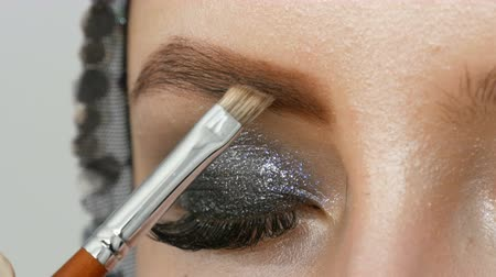 melisa : Professional makeup high fashion. The girl model draws eyebrows with a special eyebrow brush. Fashionable smoky eyes.