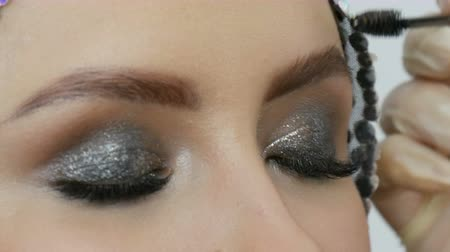 爪 : Professional makeup high fashion. The girl model draws eyebrows with a special eyebrow brush. Fashionable smoky eyes.