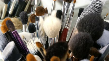 aplikatör : Set of professional brushes for make-up on table in dressing room. Fashion industry. High fashion show backstage. Makeup artist takes a brush.