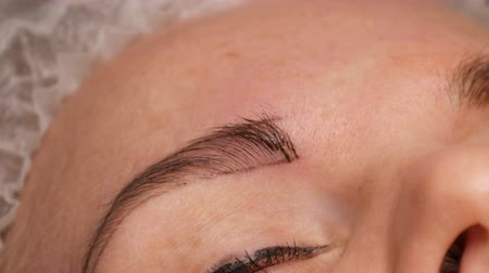 governante : Microblading eyebrow tattoo, permanent makeup. Master in gloves, using special needle, injects pigment into the skin and stains the eyebrows using hair technique, making them natural, close-up view