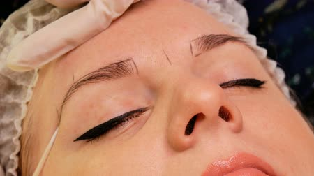 microblading : Beautician makes eyebrow correction to his patient. Marking the contour of the eyebrows with special pencil