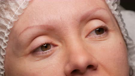 čtyřicátá léta : Forty young woman in beauty studio before eyebrow correction procedure. A face without eyebrows, old, faded eyebrow tattoo. Microblading, tattooing, powder spraying, permanent makeup